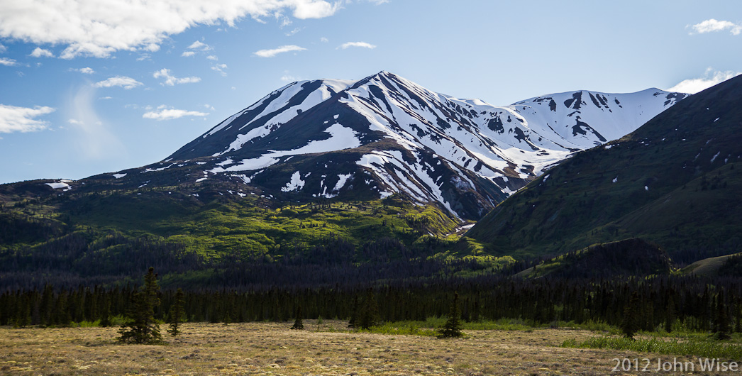 Snow covered mountains in early summer line the primitive road that is delivering us to the Alsek River